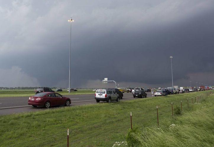 Foto de un tornado que pasó por Moore, Oklahoma, mientras automóviles se desplazaban por la carretera Interestatal 35 en el área de Indian Hills Road. (Agencias)