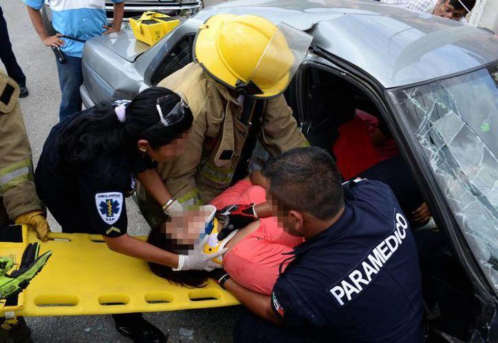 Severamente lesionada terminó la pasajera de un vehículo, luego que su padre se pasó un alto en la colonia Dolores Otero. Imagen del momento del rescate y posterior traslado al IMSS, se reporta como grave. (Milenio Novedades)