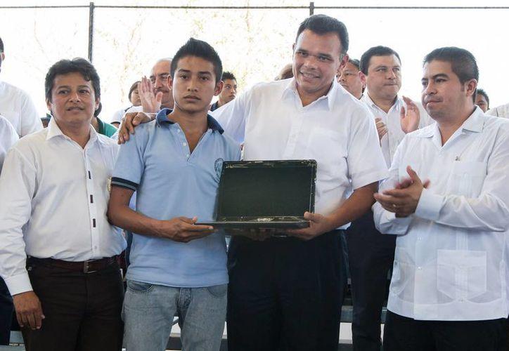 El gobernador de Yucatán, Rolando Zapata Bello, entrega una computadora portátil a un joven estudiante de Hunucmá. (Cortesía)