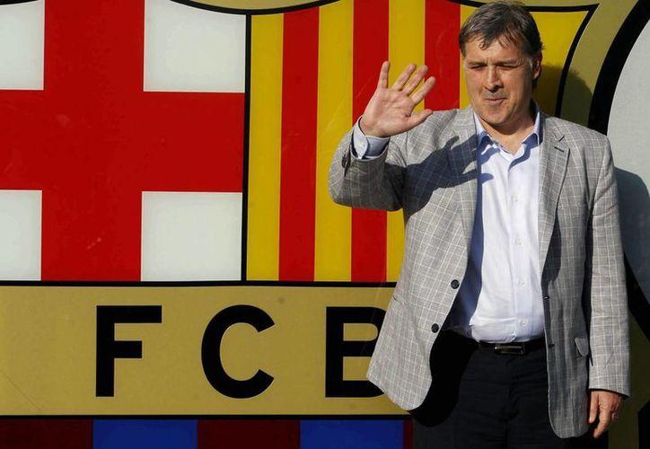'Tata' Martino, posa ante el escudo barcelonista, a su llegada a las oficinas del club azulgrana. (EFE)
