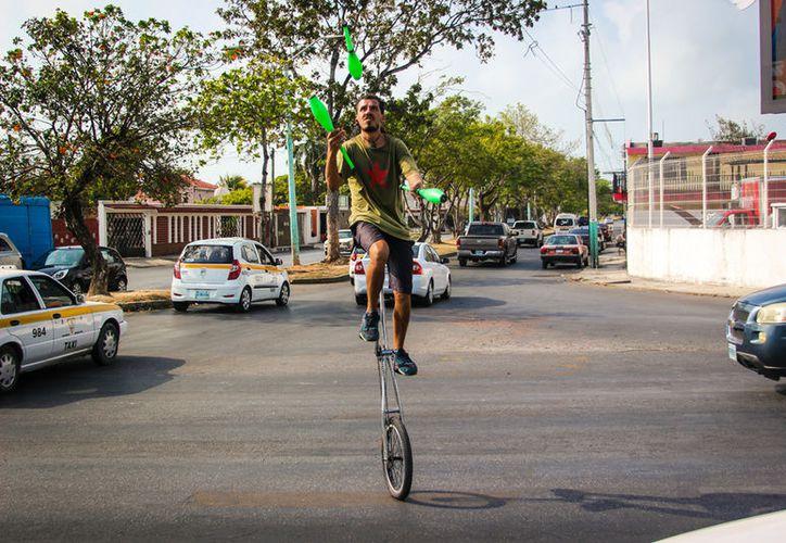 Mientras la luz del semáforo permanezca en rojo, el joven, ya en su monociclo realiza malabares con mazas y bastones. (David De La Fuente/SIPSE).