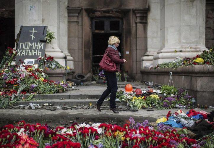 Una mujer pasa junto a las ofrendas florales por la muerte el pasado viernes de 46 personas en la Cámara de Comercio de la ciudad de Odessa. (EFE)