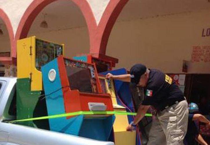Imagen de un agente federal al momento del decomiso de maquinitas tragamonedas durante un operativo en el interior del Estado. (Milenio Novedades)