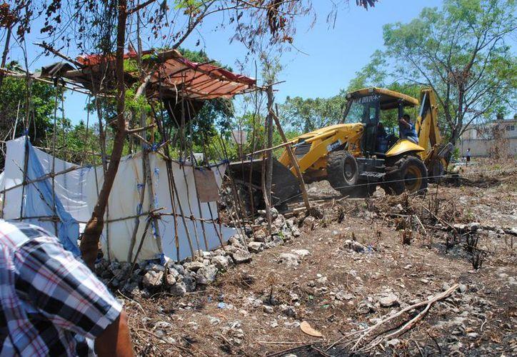 A las 7 horas entró la maquinaria para derribar las pequeñas viviendas. (Eric Galindo/SIPSE)