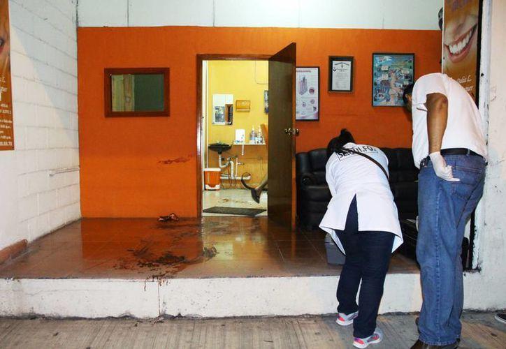 Peritos de la Fiscalía General del Estado recogen evidencias en el lugar del ataque contra una dentista en cerca del parque de la Mejorada en Mérida. (Milenio Novedades)