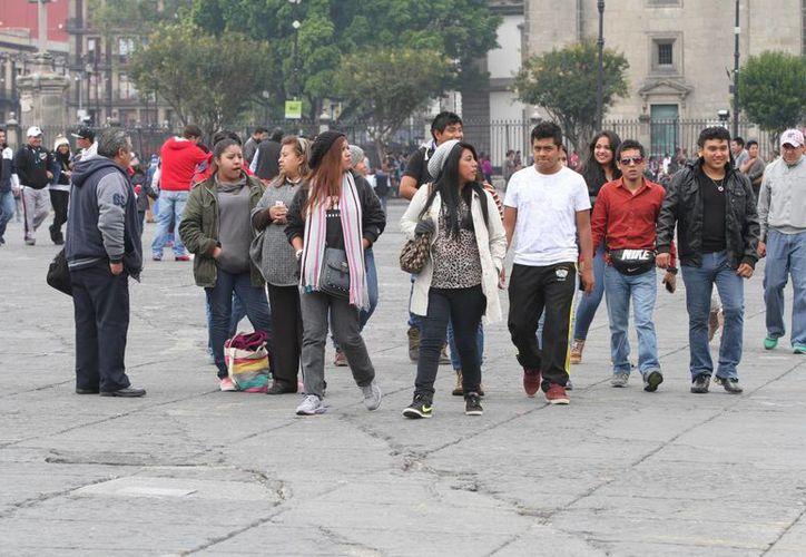 A pesar de las bajas temperaturas, los capitalinos no dejan de aprovechar sus días de descanso y se pasean por el Zócalo de la ciudad de México. (Foto: Notimex)