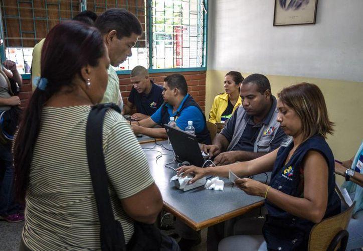 Miembros del Consejo Nacional Electoral (CNE) de Venezuela se encargan de validar algunas firmas firmas y datos personales. (EFE)