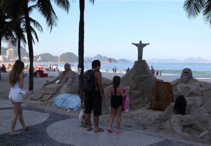 Turistas observan varias esculturas de arena, entre las que se encuentra una del papa Francisco, este 17 de julio, en la playa de Copacabana. (EFE)