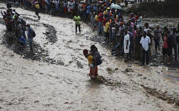 Personas intentan cruzar el río La Digue, debido al derrumbe del único puente que conecta con el sur, tras el paso del huracán Matthew, en Petit Goave, Haití. (EFE)