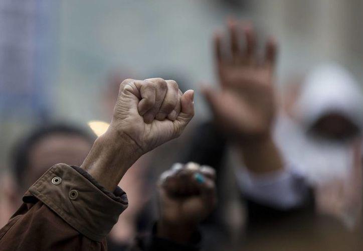 En varias ciudades de la Unión Americana se registraron marchas repudiando la decisión de no enjuiciar al policía blanco Darren Wilson, señalado por la muerte del joven negro Michael Brown. (AP)