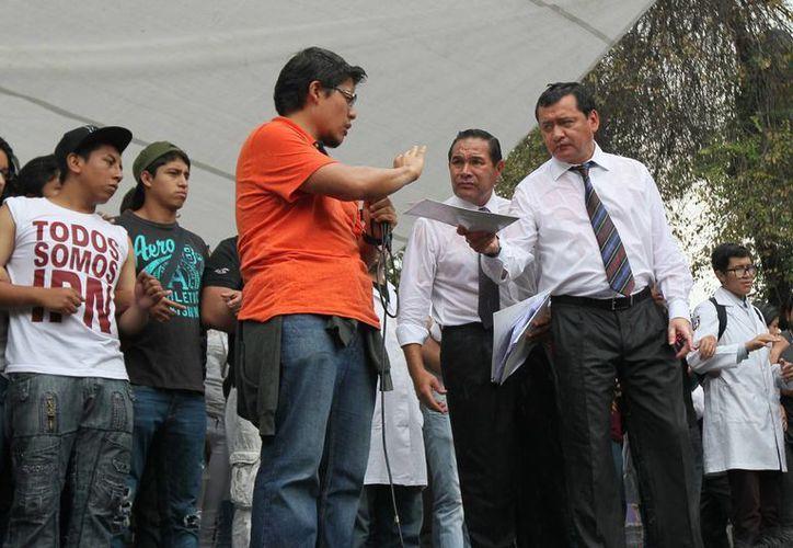 Daniel Antonio Rosales (camisa naranja) es quien ha encabezado los discursos en los mítines con el secretario de Gobernación, Miguel Osorio Chong en el Instituto Politécnico Nacional. (Foto: AP)