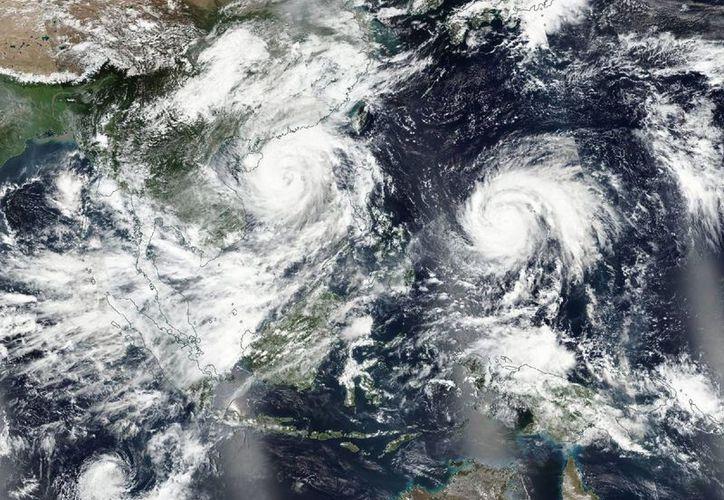Fotografía facilitada por la NASA que muestra una imagen de los tifones Sarika (c-izq) y Haima (c-d) sobre el océano Pacífico. (EFE)