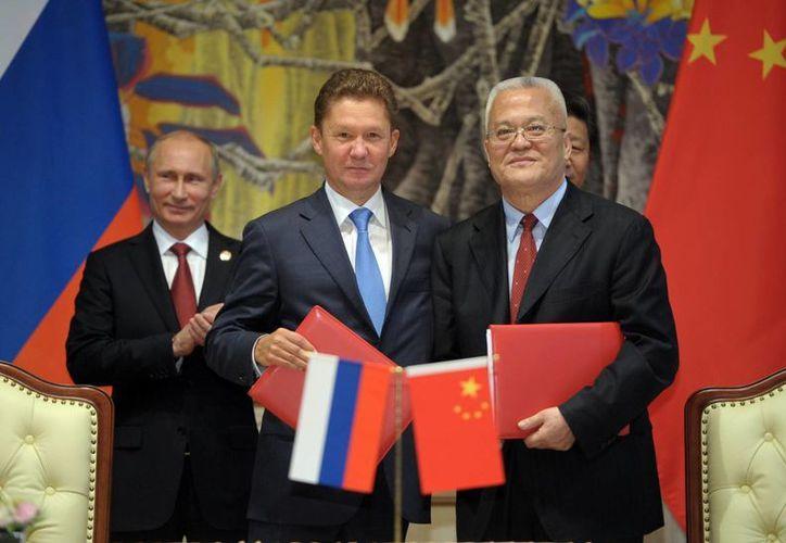 Putin aplaude durante la ceremonia de firma de acuerdos, mientras que Alexei Miller, director ejecutivo de la empresa rusa Gazprom, centro, y Zhou Jiping, director de la compañía china CNPC, posan con los documentos respectivos. (Agencias)