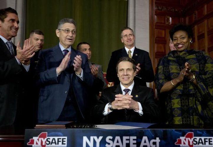 La Asamblea de Nueva York aprobó la iniciativa de ley para el control de armas más dura de EU y el gobernador Andrew Cuomo (c) la promulgó momentos después. (Agencias)