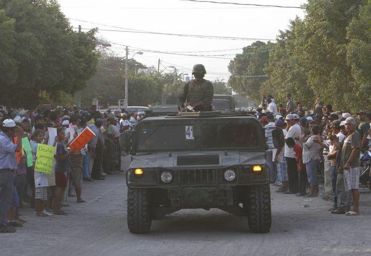 Los residentes saludan los soldados del ejército mexicano al entrar en el pueblo de La Ruana, Michoacán. (Agencias)