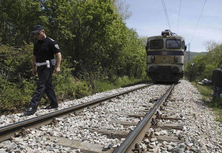 Un policía camina junto a las vías de un tren en Veles, un pueblo en el centro de Macedonia, donde unos 14 migrantes al parecer de Afganistán y Somalia fueron arrollados. (AP/Boris Grdanoski)