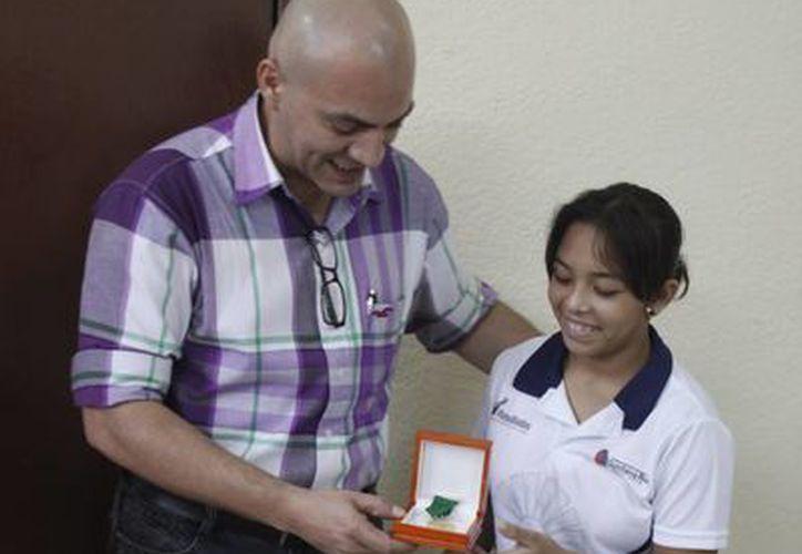 El oficial mayor Omar Escalante Muza entregando una de las preseas a Nahomí Hoyos Domínguez. (Harold Alcocer/SIPSE)