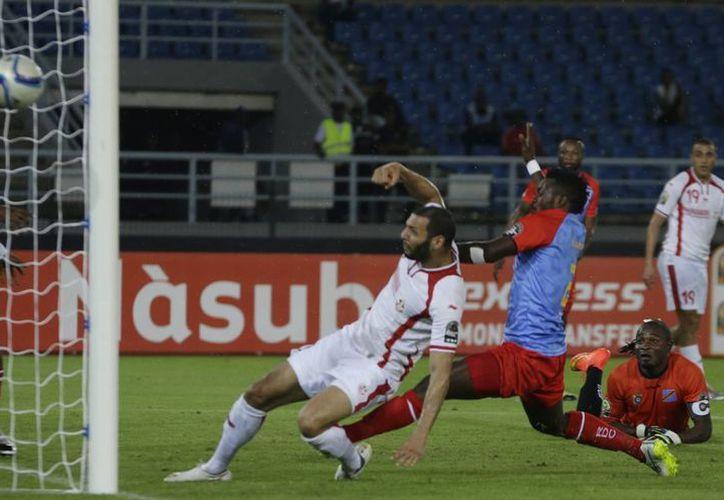 El portero de RD Congo, Robert Muteba Kidiaba (al fondo, d), observa al tunecino Yassine Chikhaoui (i) conectar el balón para meter gol en partido de la Copa Africana. (Foto:AP)