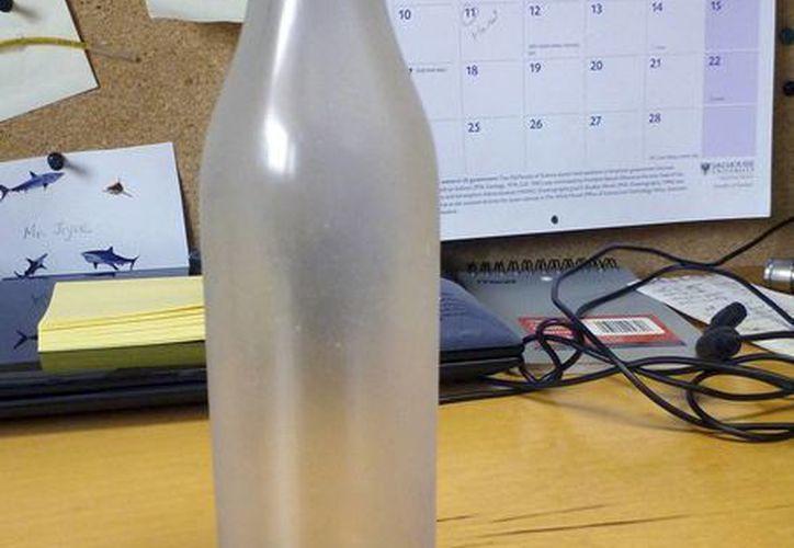 """Un 75% de la superficie de la botella había quedado esmerilada por la acción de la arena, pero que todavía podía leer la inscripción """"Rompa esta botella"""". (Agencias)"""