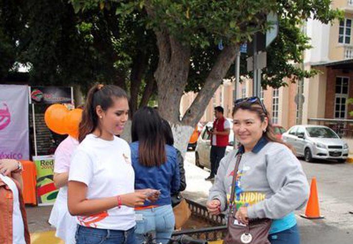 Integrantes de Red Mujeres X México Yucatán promovieron ayer la no violencia contra las mujeres, cuya conmemoración es hoy, Día Naranja. Fotografía de una joven que repartió volantes del evento a un costado del Monumento a la Patria. (Milenio Novedades)