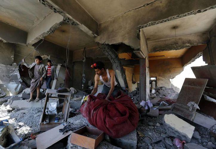 Varias personas inspeccionan entre los escombros de una vivienda destruida tras un ataque de la coalición liderada por Arabia Saudí, en Saná. (EFE)