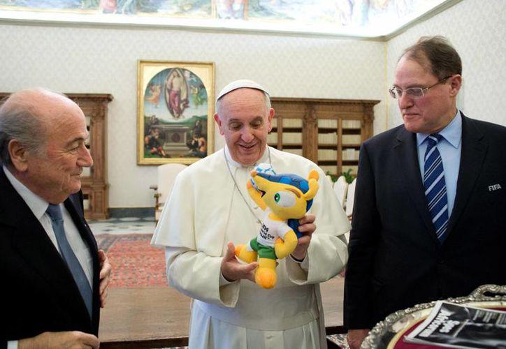 Blatter intercambió impresiones y regalos en el Vaticano con el Papa, quien sostiene a Fuleco, mascota del Mundial de Brasil. (Agencias)