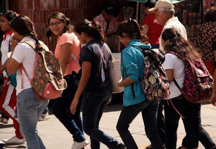 El primer paso de los alumnos de licenciatura para incorporarse al mercado laboral es el servicio social. Imagen de contexto de un grupo de jóvenes estudiantes mientras cruzan una calle en el centro de Mérida. (Milenio Novedades)
