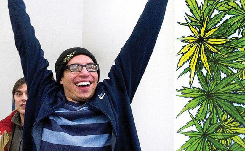 El primer comprador de marihuana legal en Colorado festeja su adquisición. (Agencias)