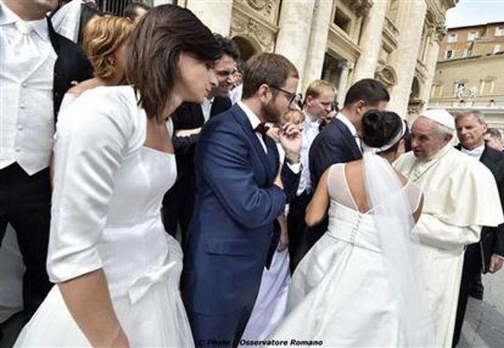El Papa Francisco habla con recién casados durante su audiencia general semanal en la Plaza de San pedro en el Vaticano. (L'Osservatore Romano/Pool Foto via AP)