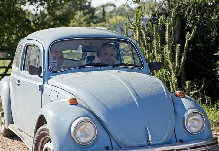 El presidente José Mujica y su esposa, la senadora Lucía Topolansky, dan un paseo en el Volkswagen del Mandatario, por el cual le han ofrecido un millón de dólares. (Agencias)