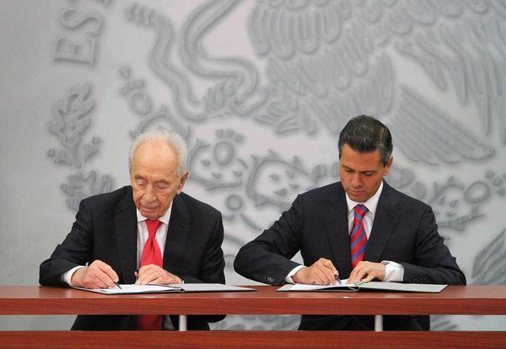 El presidente de la República, Enrique Peña Nieto, y su homólogo de Israel, Shimon Peres al momento de realizar la firma. (Notimex)