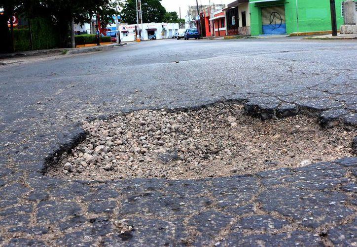 La calle 95 por 60 del centro, en la esquina de los Cocos, presenta un enorme bache. (José Acosta/Milenio Novedades)