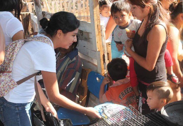 Universitarios de la Uady llevaron a habitantes de la colonia San Antonio Xluch III, ropa, acciones de educación y recreación, y el servicio de energía eléctrica. (Fotos cortesía del Gobierno)