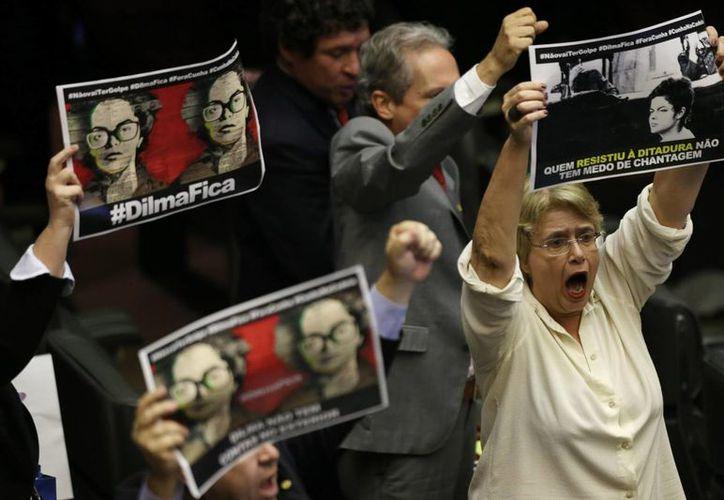 """Los legisladores que apoyan a la presidenta Dilma Rousseff sostienen fotografías de la líder cuando era presa política, con el texto en portugués: """"Dilma quédate"""", durante una sesión de la Cámara Baja de ese país. Suspenden por una semana el juicio político en contra de la Presidenta. (Foto AP / Eraldo Peres)"""