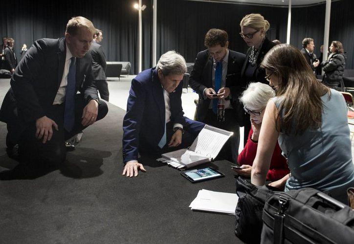En Lausa Suiza, el secretario de Estado de EU, John Kerry, observa en una tablet al presidente Barack Obama quien desde Washington dirigió un mensje al conocer el acuerdo sobre el programa nuclear iraní. (Foto: AP/Brendan Smialowski, Pool)