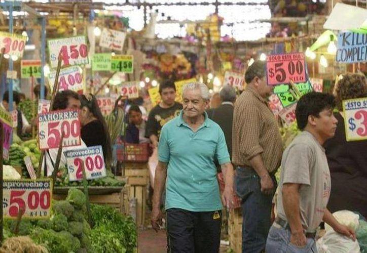 Bajó el costo de la cebolla, chile serrano, limón, papaya, huevo, etc. Imagen de un hombre que camina en un mercado municipal. (Archivo/SIPSE)