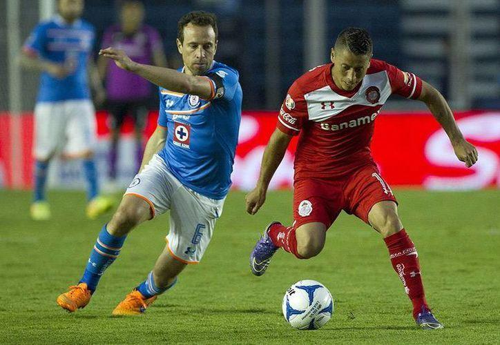 Los cruzazulinos dirigidos por Tomás Boy, suman 14 unidades que los ubica en la séptima posición del torneo mexicano. En la foto, Gerardo Torrado (I) pelea el balón en el encuentro frente al Toluca. (Notimex)