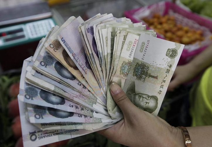 China devaluó hoy su moneda en 1.86 por ciento, la mayor caída desde 1994, frente al dólar. Una vendedora muestra billetes de yuan en Pekín, China. (EFE)