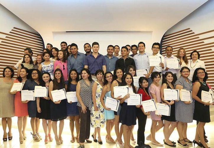 La primera generación de egresados de la Licenciatura en Turismo por la Uady está integrada por 33 jóvenes. La imagen es de la entrega de constancias de pertenencia en  el Auditorio de la Facultad de Antropología. (Uady)