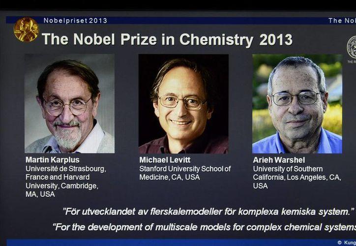 Detalle de una pantalla en la que aparecen las fotografías de los científicos galardonados con el Premio Nobel de Química 2013. (EFE)
