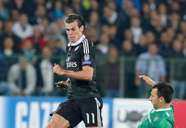 Gareth Bale (de frente) y Dyakov disputan un balón durante el encuentro en el que Real Madrid derrotó 2-1 al Ludogorets, en Bulgaria, en fase de grupos de la Copa de Campeones de Europa. (AP)