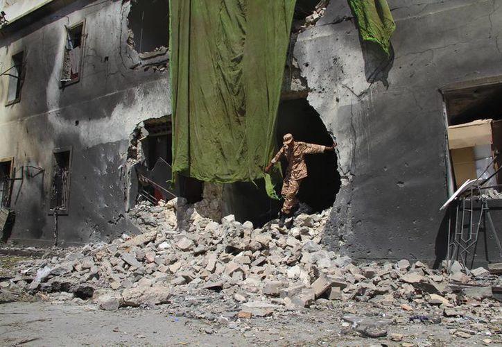Un soldado libio sale de un edificio destruido en una fuerte explosión. (EFE/Archivo)