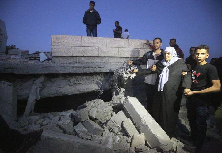 Varias personas observan los restos de una casa que fue destruida por el ejército israelí en Halhoul, al norte de Hebrón. (EFE)