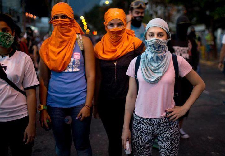 Mujeres manifestantes anti-gubernamentales llevan camisetas sobre sus caras para ocultar su identidad durante los enfrentamientos con las fuerzas de seguridad en Caracas, Venezuela. (Agencias)