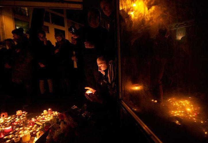 El día después de los ataques terroristas en París, muchas personas se acercaron a los sitios de la tragedia para colocar ofrendas por lo muertos. En la imagen, una mujer coloca una veladora a las afueras del restaurante Belle Equipe. (AP)