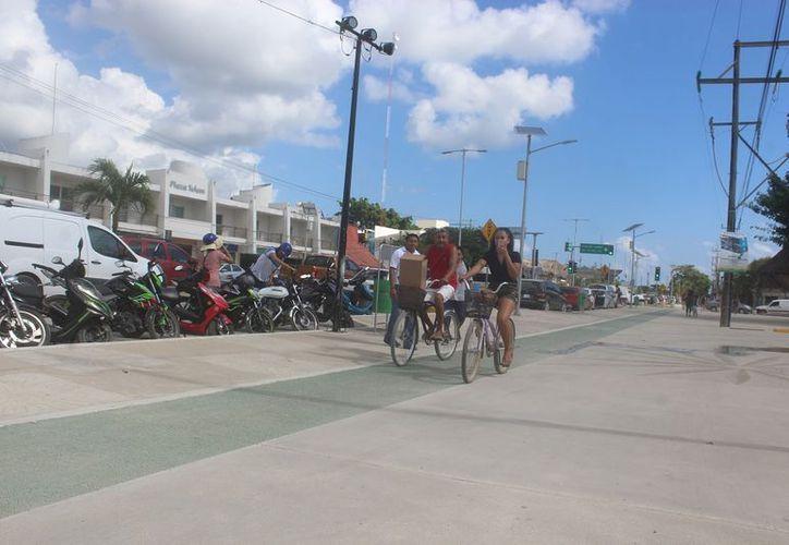 Tres personas recorren el camino invitando a los ciclistas a hacer uso de él. (Sara Cauich/SIPSE)