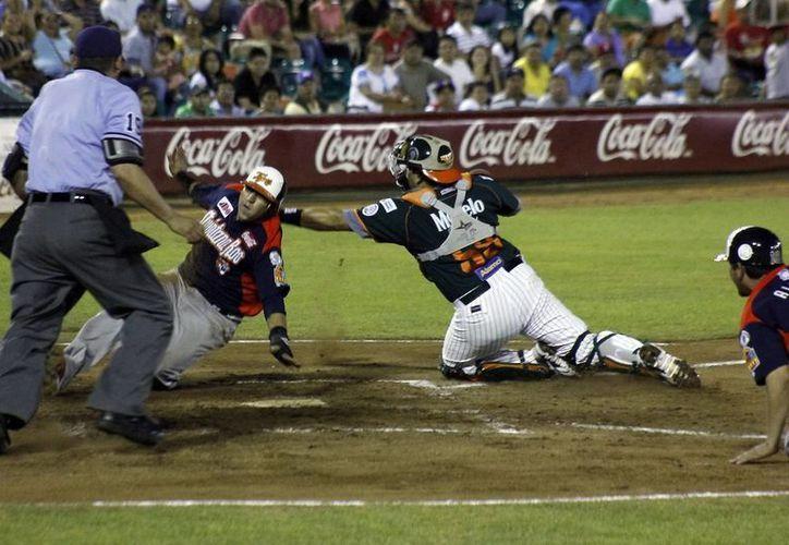 El tigre Carlos Gastélum evade al cátcher león Said Gutiérrez para anotar carrera en la tercera entrada. (Juan Albornoz/SIPSE)