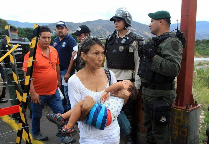 Colombianos regresan a su país desde Venezuela a través de un filtro impuesto por la guardia en el puente internacional Simón Bolívar. (EFE)