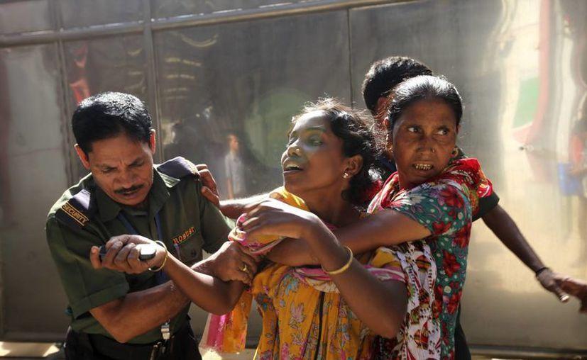Un agente de policía sujeta a una mujer que intenta entrar a la fábrica textil. (EFE)