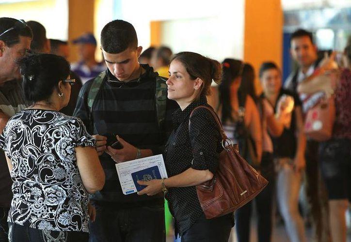 Una mujer conversa con sus familiares antes de viajar en el aeropuerto José Martí de La Habana, Cuba. (EFE)